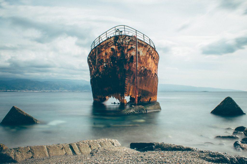 kryzys w firmie - jak uratować firmę przed utonięciem? zdjęcie przedstawiające zardzewiały statek przy brzegu
